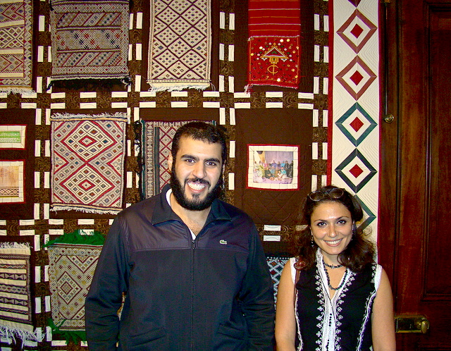 Mohamed Alshubrumi and Benan Grams in front of the Moroccan Amizigh Quilt. The quilt squares were woven at the Ain Leuh Weavers cooperative where they served as Fellows in 2013.