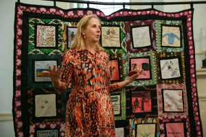 Sarah Craven in front of the Gulu Disability Quilt. Sarah attends the Westmoreland church and made the connection with AP.
