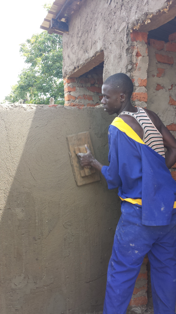 A construction worker evening out the cement walls of the new latrine