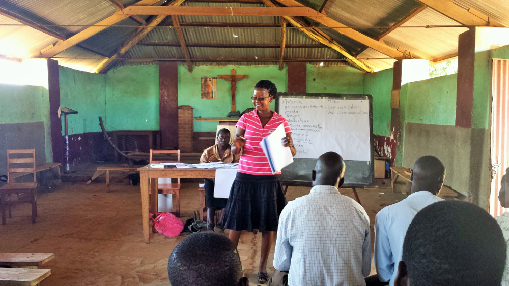 Emma, an office assistant at GDPU, discussing language and labeling with teachers at Koch Goma Central