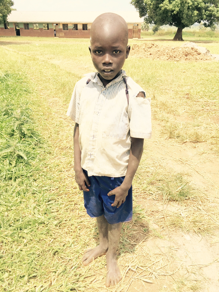 A boy student at Tochi Primary School on his way to class after using the latrines