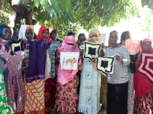 A group of survivors with outreach coordinator, Mariam Seck, showing off their embroidery
