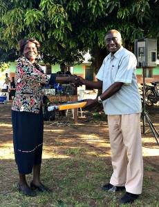 Head Teacher Madam Christine Accepting an Award from Local Council Chairman Mr Okumu Luriu