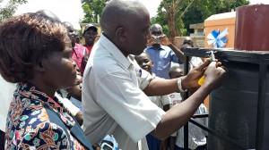 Local Council Chairman Mr Okumu Luriu Opening the Locks on the Toilet's Water Tank with Head Teacher Madam Christine