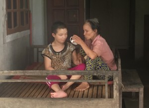 Pham Thi Do caring for her daughter Luyen, who is afflicted with cerebral palsy.