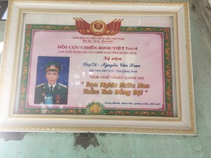 A certificate recognizing Mr. Xoan's military service, displayed proudly in his home. Mr. Xoan has relocated to Hue to care for his ailing son.