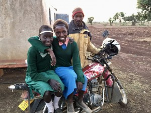 Helen, left, and Chebet, center, smile on Lotit's motorcycle moments after meeting