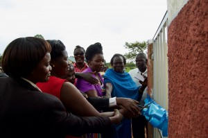 District officials and school leadership cut the ribbon on the new accessible latrine at Ogul Primary School.